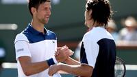 Petenis Serbia Novak Djokovic memberikan selamat kepada Taro Daniel asal Jepang setelah dikalahkan pada putaran kedua Indian Wells, Minggu (11/3/2018). (MATTHEW STOCKMAN / GETTY IMAGES NORTH AMERICA / AFP)