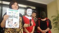 Fiqih Adiyatma (topeng putih), mucikari pijat gay yang diringkus Unit PPA Polrestabes Surabaya. (Dida Tenola/JawaPos.com)