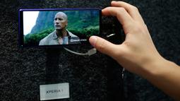 Penunjung menonton film di smartphone Sony Xperia 1 dalam gelaran Mobile World Congress (MWC) 2019 di Barcelona, Spanyol, Kamis (28/2). (Pau Barrena/AFP)