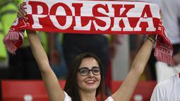 Suporter wanita tersenyum sambil membentangkan syal sebelum pertandingan grup H Piala Dunia 2018 antara Polandia melawan Senegal di Stadion Spartak di Moskow, Rusia (19/6). Dalam pertandingan ini Polandia takluk atas Senegal 2-1. (AFP Photo/Franck Fife)
