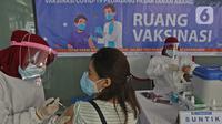 Seorang wanita menjalani vaksinasi COVID-19 di Pasar Tanah Abang Blok A, Jakarta, Rabu (17/2/2021). Vaksinasi COVID-19 tahap kedua yang diberikan untuk pekerja publik dan lansia itu dimulai dari pedagang Pasar Tanah Abang di blok A, B, F, dan G. (Liputan6.com/Herman Zakharia)