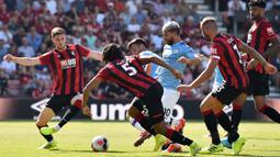 Striker Manchester City, Sergio Aguero, berusaha melewati pemain Bournemouth pada laga Premier League 2019 di Stadion Vitality, Minggu (25/8). Manchester City menang 3-1 atas Bournemouth. (AFP/Glyn Kirk)