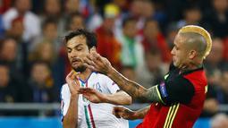 Gelandang Belgia, Radja Nainggolan (kanan) berebut bola dengan gelandang Italia, Marco Parolo pada pertandingan grup E Piala Eropa di Stade de Lyon, Prancis, (14/6). Italia menang atas Belgia dengan skor 2-0. (REUTERS/Kai Pfaffenbach)