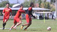 Gelandang Arema, Hanif Sjahbandi ditarik Vikrian Akbar dalam latihan terakhir 30 Oktober lalu di Lapangan Balearjosari, Kota Malang. (Bola.com/Iwan Setiawan)