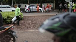 Kondisi lalu lintas saat petugas pertamanan membersihkan tanaman dan rumput yang rusak terinjak-injak usai unjuk rasa massa Partai Hanura di depan Gedung KPU, Jakarta, Senin (21/1). (Liputan6.com/Faizal Fanani)