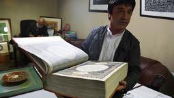 Seorang seniman Afghanistan, Abdull Sabur Omari menunjukkan Alquran buatan tangan di Mourad Khani, Kabul, Afghanistan (19/4). Kitab suci Alquran ini dibuat dengan tangan secara manual di atas kain sutra. (AFP/Wakil Kohsar)