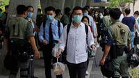 Polisi anti huru hara memeriksa kartu identitas orang-orang di dekat Gedung Dewan Legislatif di Hong Kong, Rabu (27/5/2020). Penjagaan ekstra dilakukan menimbang kemungkinan aksi menentang RUU yang mengkriminalkan penghinaan terhadap lagu kebangsaan China. (AP Photo/Kin Cheung)