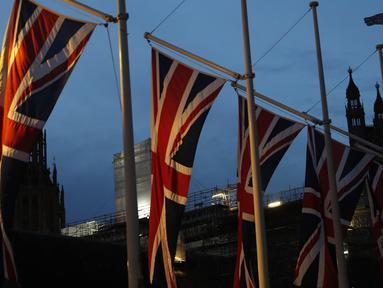 Bendera Inggris berkibar dengan latar Istana Westminster terlihat di London, Sabtu, (1/2/2020).  Mulai 1 Februari 2020 ini, Inggris secara resmi telah meninggalkan Uni Eropa (UE) setelah lebih dari tiga tahun referendum yang membuat negara itu terpecah belah. (AP Photo/Alastair Grant)