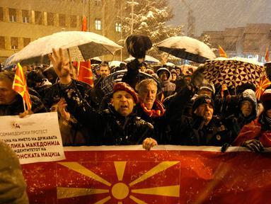 Warga membentangkan bendera Macedonia saat menggelar protes di depan gedung Parlemen, Skopje, Selasa (27/2). Di tengah hujan salju dan temperatur ekstrem, mereka turun ke jalan memprotes wacana pengubahan nama negara mereka. (AP/Boris Grdanoski)
