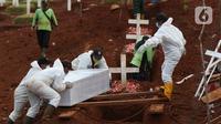 Petugas mendorong peti jenazah yang akan dimakamkan dengan protokol COVID-19 di TPU Pondok Ranggon, Jakarta, Sabtu (17/10/2020). Pada Sabtu (17/10), 32 jenazah dimakamkan dengan protokol COVID-19 di TPU Pondok Ranggon. (Liputan6.com/Helmi Fithriansyah)