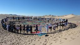 Peserta menghadiri kelas yoga yang diselenggarakan oleh komunitas YSYoga System di gurun Samalayuca, negara bagian Chihuahua, Meksiko pada 25 Mei 2019. Latihan di atas pasir gurun yang terik ini menjadi tantangan tersendiri bagi para pencinta Yoga. (Herika MARTINEZ/AFP)