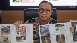Karopenmas Divisi Humas Polri Brigjen Pol Dedi Prasetyo menunjukkan barang bukti kasus pemberitaan hoax di Jakarta, Senin (1/7/2019). Dalam pengungkapan kasus tersebut kepolisian menangkap pelaku penyebar berita hoax dengan akun media sosial bernama /rif_oposite. (Liputan6.com/Faizal Fanani)