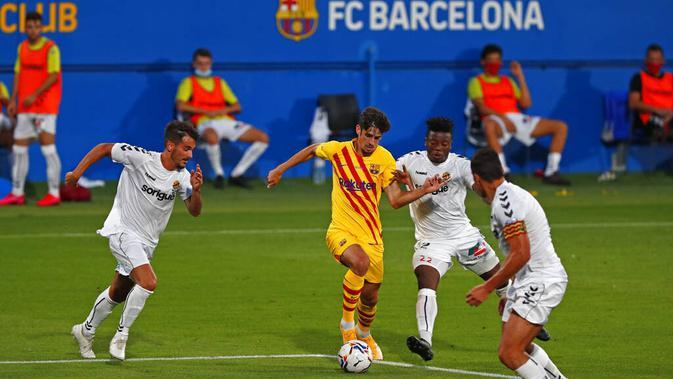 Pemain Barcelona, Trincao, berusaha melewati pemain Gimnastic pada laga uji coba di Johan Cruyff Stadium, Minggu (13/9/2020). Barcelona menang dengan skor 3-1. (AP/Joan Monfort)