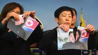 Warga Korea Utara yang membelot menunjukkan foto pemimpin Korea Utara Kim Jong-Un yang dirobek saat konferensi pers di Majelis Nasional di Seoul (24/1). (AFP Photo/Jung Yeon-Je)