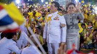 Raja Maha Vajiralongkorn dan Ratu Suthida melambaikan tangan ke pendukungnya di Bangkok, Thailand, Minggu (1/11/2020). Di bawah tekanan yang meningkat dari pengunjuk rasa yang menuntut reformasi pada monarki, Raja dan Ratu Thailand bertemu dengan ribuan pendukungnya. (AP Photo/Wason Wanichakorn)