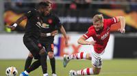 Gelandang AZ Alkmaar, Frederik Midtsjo, dijatuhkan gelandang Manchester United, Fred, pada laga Liga Europa di Stadion ADO, The Hague, Kamis (3/10). Kedua klub bermain imbang 0-0. (AP/Peter Dejong)