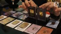 Karyawan menunjukkan kepingan emas yang dijual di Galeri 24, Jakarta, Selasa (15/12/2020). Harga emas hasil produksi PT Aneka Tambang Tbk (Antam) atau emas Antam kini turun Rp 1.000 per gram menjadi Rp 951 per gram pada perdagangan, Selasa (15/12). (Liputan6.com/Angga Yuniar)