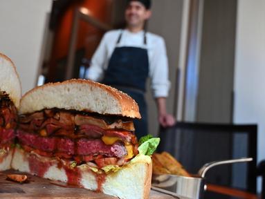 Chef dari restoran The Oak Door, Patrick Shimada berpose dengan burger raksasa di hotel Grand Hyatt Tokyo, Senin (1/4). Restoran itu membuat hamburger wagyu seukuran bola sepak yang disajikan dengan roti bertabur emas untuk merayakan penobatan kaisar baru Jepang bulan depan. (CHARLY TRIBALLEAU/AFP)