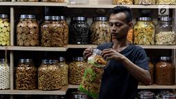 Pedagang memasukan kue kering di Pasar Mayestik, Jakarta Selatan, Senin (11/6). Separuh Ramadan dan jelang lebaran masyarakat mulai berburu kue kering. (Liputan6.com/Johan Tallo)