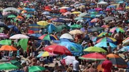 Kerumunan pengunjung berkumpul di pantai setelah masa pelonggaran pembatasan sosial akibat covid-19 di Bournemouth, Kamis (25/6/2020). Menurut ramalan cuaca, Inggris mengalami hari terpanas tahun ini dengan suhu yang diperkirakan akan meningkat lebih tinggi. (Andrew Matthews/PA via AP)