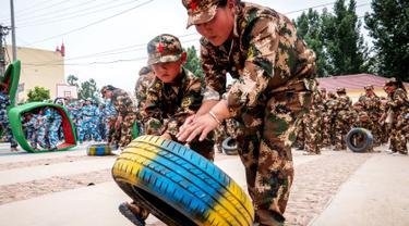 Sejumlah anak-anak mendorong ban saat mensimulasikan latihan militer di sebuah taman kanak-kanak di provinsi Henan, China (30/5). Latihan militer ini dilakukan untuk menjelang Hari Anak Internasional yang jatuh pada 1 Juni. (AFP)