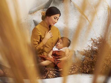 Sarwendah terlihat begitu keibuan saat dirinya mengenakan kebaya warna kuning. Ia tampak begitu anggun saat memangku buah hatinya, Thalia Ruben Onsu. (Foto: instagram.com/sarwendah29)