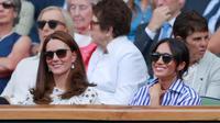 Duchess of Cambridge Kate Middleton dan Duchess of Sussex Meghan Markle tersenyum saat menyaksikan pertandingan Serena Williams dan Angelique Kerber di kejuaraan  tenis Wimbledon di London, Inggris, (14/7). (AP Photo/Andrew Couldridge)
