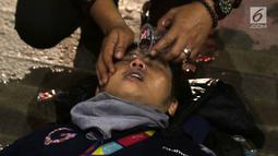 Seorang pria mendapat perawatan setelah menjadi korban dalam demonstrasi berujung ricuh di Pejompongan, Jakarta, Rabu (25/9/2019). Sebelumnya, ribuan pelajar yang melangsungkan demonstrasi di Gedung DPR terlibat bentrok dengan polisi. (Liputan6.com/Helmi Fithriansyah)