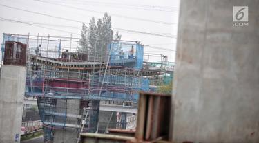 Pekerja menyelesaikan pembangunan proyek Light Rail Transit (LRT) Jabodebek fase I di kawasan Cawang, Jakarta, Senin (14/1). Progres konstruksi stasiun LRT Cawang, Jakarta Timur sudah mencapai 62,2 persen. (Liputan6.com/Faizal Fanani)
