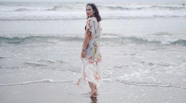 Ini gaya santai Pamela saat sedang di pantai. Mengenakan dress dengan motif bunga, yang dipadupadankan dengan pakaian berwarna hitam di dalamnya dan kacamata gelap. (Liputan6.com/IG/@pammybowie)