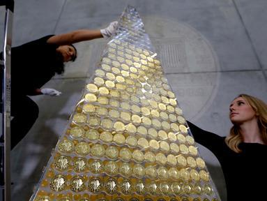 Karyawan rumah emas ProAurum menyusun koin emas yang disebut sebagai pohon Natal di Munich, Jerman, 3 Desember 2018. Pohon Natal ini terbuat dari 2.018 koin emas filharmonik wina senilai 2.3 euro atau sekitar 370 milliar rupiah. (AP/Matthias Schrader)