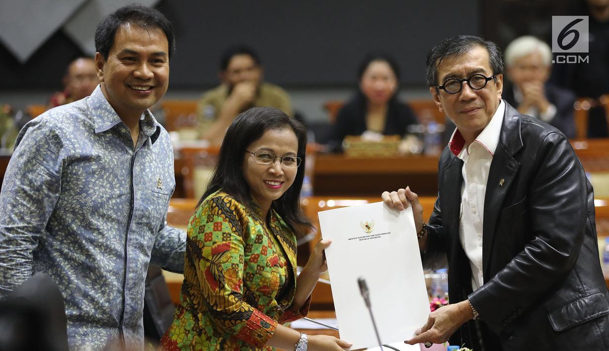 Menkumham Yasonna Laoly (kanan) menunjukkan dokumen saat rapat pleno terkait amnesti untuk Baiq Nuril dengan Komisi III DPR di Gedung Nusantara II, Jakarta, (24/7/2019). DPR setuju Presiden Joko Widodo atau Jokowi memberikan amnesti kepada Baiq Nuril. (Liputan6.com/JohanTallo)