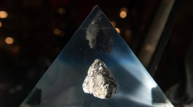 Batu dari Bulan terpajang dalam wadah kaca akrilik jelang perayaan 50 tahun misi Apollo di atas kapal USS Hornet, Alameda, California, Amerika Serikat, Selasa (16/7/2019). Astronot menyimpan batu Bulan ke dalam kotak penyimpanan dan membawanya ke Bumi. (JOSH EDELSON/AFP)