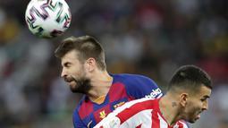Bek Barcelona, Gerard Pique menyundul bola melewati pemain Atletico Madrid Angel Correa pada laga semifinal Piala Super Spanyol di King Abdullah Sports City, Jeddah, Kamis (9/1/2020). Barcelona harus menjalani pertandingan yang dramatis saat kalah 2-3 dari Atletico Madrid. (AP/Hassan Ammar)