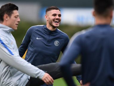 Striker Inter Milan, Mauro Icardi (tengah) tersenyum saat sesi latihan di tempat pelatihan Appiano Gentile dekat Milan, Italia (5/11). Inter akan bertanding melawan Barcelona pada lanjutan grup B Liga Champions. (AFP Photo/Miguel Medina)