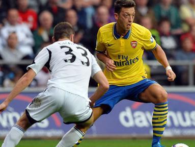 Pemain Arsenal Mesut Ozil dihadang Pemain Swansea City Ben Davies Pada pertandingan Liga Premier Inggris antara Swansea City dan Arsenal di Stadion Liberty di Swansea (28/09/13). (AFP/Paul Ellis)