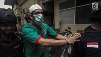 Artis Claudio Martinez memakai masker dengan tangan di borgol usai rilis narkoba di Polres Jakarta Barat, Jumat (9/11). Claudio ditangkap dengan barang bukti 7,96 gram ganja. (Liputan6.com/Faizal Fanani)