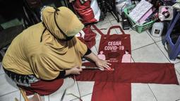 Siti Zahro (44) menggaris pola saat menyelesaikan pembuatan celemek dari tas bansos Covid-19 di industri jahit rumahan KG-Lupe Fashion, Salemba, Jakarta, Senin (16/11/2020). Dalam sehari Siti mampu memproduksi tiga buah celemek. (merdeka.com/Iqbal S. Nugroho)