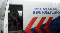 Warga duduk dalam mobil saat mengurus SIM di Pelayanan SIM Keliling, Tangerang Selatan, Banten, Jumat (7/8/2020). Ditlantas Polda Metro Jaya memberi dispensasi bagi pemilik SIM yang masa berlakunya habis di masa pandemi COVID-19 bisa memperpanjang sampai akhir Agustus 2020. (merdeka.com/Dwi Narwoko)