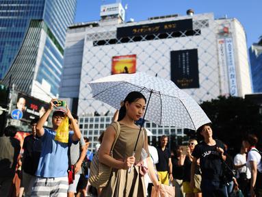 Seorang wanita menggunakan payung untuk melindungi dirinya dari sinar matahari selama gelombang panas saat melintas di distrik Shibuya Tokyo, Minggu (4/8/2019). Setelah menyerang beberapa wilayah di Eropa, suhu tinggi juga terjadi di Jepang. (Charly TRIBALLEAU / AFP)