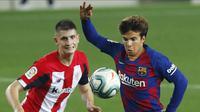 Pemain Barcelona, Riqui Puig, berebut bola dengan pemain Athletic Bilbao, Oihan Sancet, pada laga La Liga di Stadion Camp Nou, Selasa (23/6/2020). Barcelona menang 1-0 atas Athletic Bilbao. (AP/Joan Monfort)