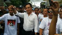 Yusril berjalan ke lokasi acara dan melambaikan tangan dari jauh pada warga Bidara Cina. (Nanda Perdana Putra/Liputan6.com)