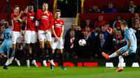 Tendangan bebas pemain City, Aleksandar Kolarov yang dihadang para pemain MU pada pertandingan Piala Liga Inggris di Stadion Old Trafford, Manchester, Inggris (26/10). (Reuters/Jason Cairnduff)
