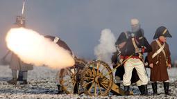 Penggemar sejarah mengenakan kostum tentara menembakan meriam saat melakukan adegan perang Napoleon yang terkenal di Austerlitz, Republik Ceko (2/12). Acara ini untuk memperingati pertempuran Austerlitz ke-212. (AP Photo/Petr David Josek)