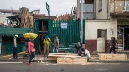 Mr. Jean bersama timnya membuat peti mati murah di jalan, padahal kegiatan ini dilarang di jalan raya umum, di Antananarivo, Madagaskar, Rabu (14/4/2021). Peti mati dari kayu pinus yang diproduksi selama satu jam tersebut dijual antara Rp 350ribu hingga Rp 820ribu. (RIJASOLO/AFP)