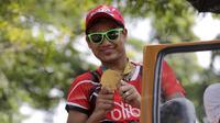 Tontowi Ahmad memamerkan medali emas Olimpiade Rio 2016 di tengah kemeriahan penyambutan kirab bersama Liliyana Natsir di kota Kudus, Kamis (1/9/2016). (Bola.com/Arief Bagus).
