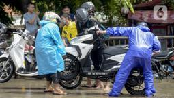 Pengendara motor membuang air yang masuk ke dalam knalpot saat melintasi banjir di Jalan Husein Nastranegara Perapatan Rawa Bokor, Tangerang, Sabtu (1/2/2020). Hujan deras yang mengguyur sejak Jumat (31/1) malam menyebabkan sejumlah kawasan di Tangerang terandam air. (merdeka.com/Imam Buhori)