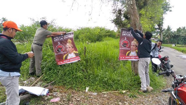 Petugas mencopot APK yang melanggar aturan pemasangan. Di antaranya, poster Jokowi bermahkota alias Jokowi raja. (Liputan6.com/Panwas Banyumas/Muhamad Ridlo)