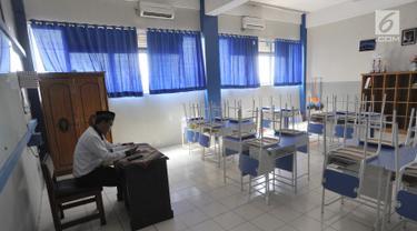 Seorang guru beraktivitas di ruang kelas yang kosong di Mts Annajah, Petukangan, Jakarta Selatan, Senin (5/8/2019). Masih padamnya listrik di sejumlah kawasan Jakarta membuat kegiatan belajar mengajar terganggu hingga memaksa pihak sekolah memulangkan siswa lebih awal. (merdeka.com/Arie Basuki)