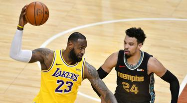 Pebasket Los Angeles Lakers, LeBron James, berusaha melewati pebasket Memphis Grizzlies, Dillon Brooks, pada laga NBA, Rabu (6/1/2021). LA Lakers menang tipis 94-92 atas Grizzlies. (AP Photo/Brandon Dill)